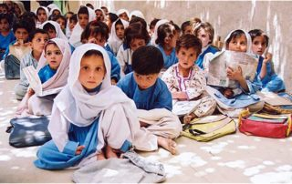 Elementray shcoll children, mostly girls, seated on the floor in school classroom