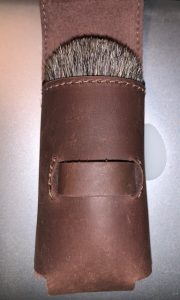 Leather pouch with a brush head in it